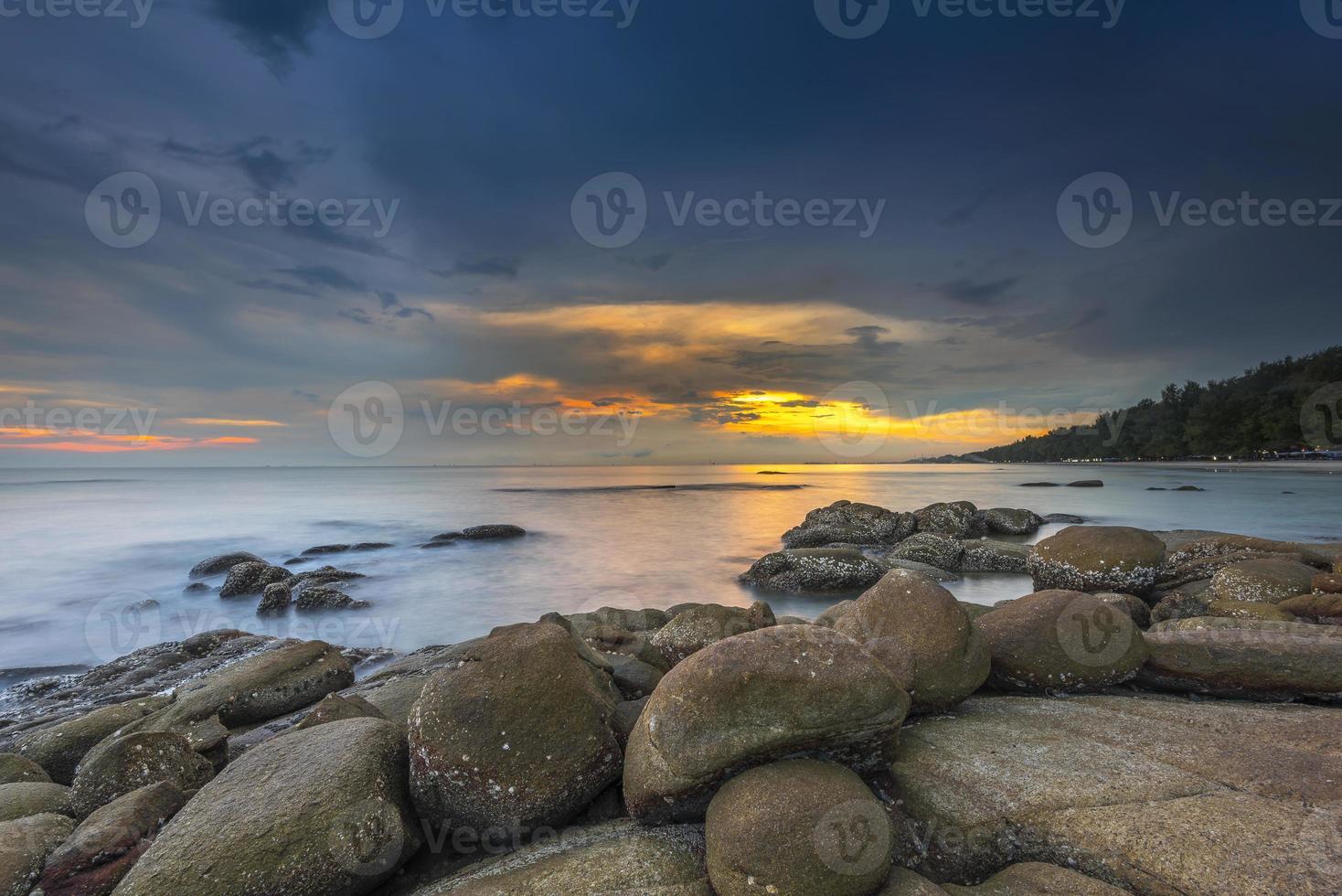 mer avec un coucher de soleil et le ciel nuageux photo