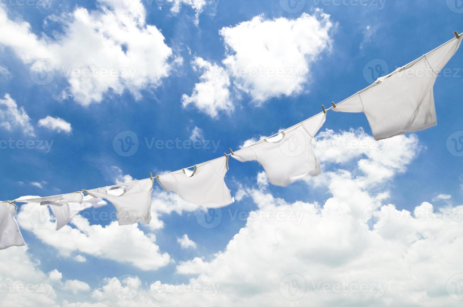 Vêtements blancs sur une corde à linge contre un ciel nuageux photo