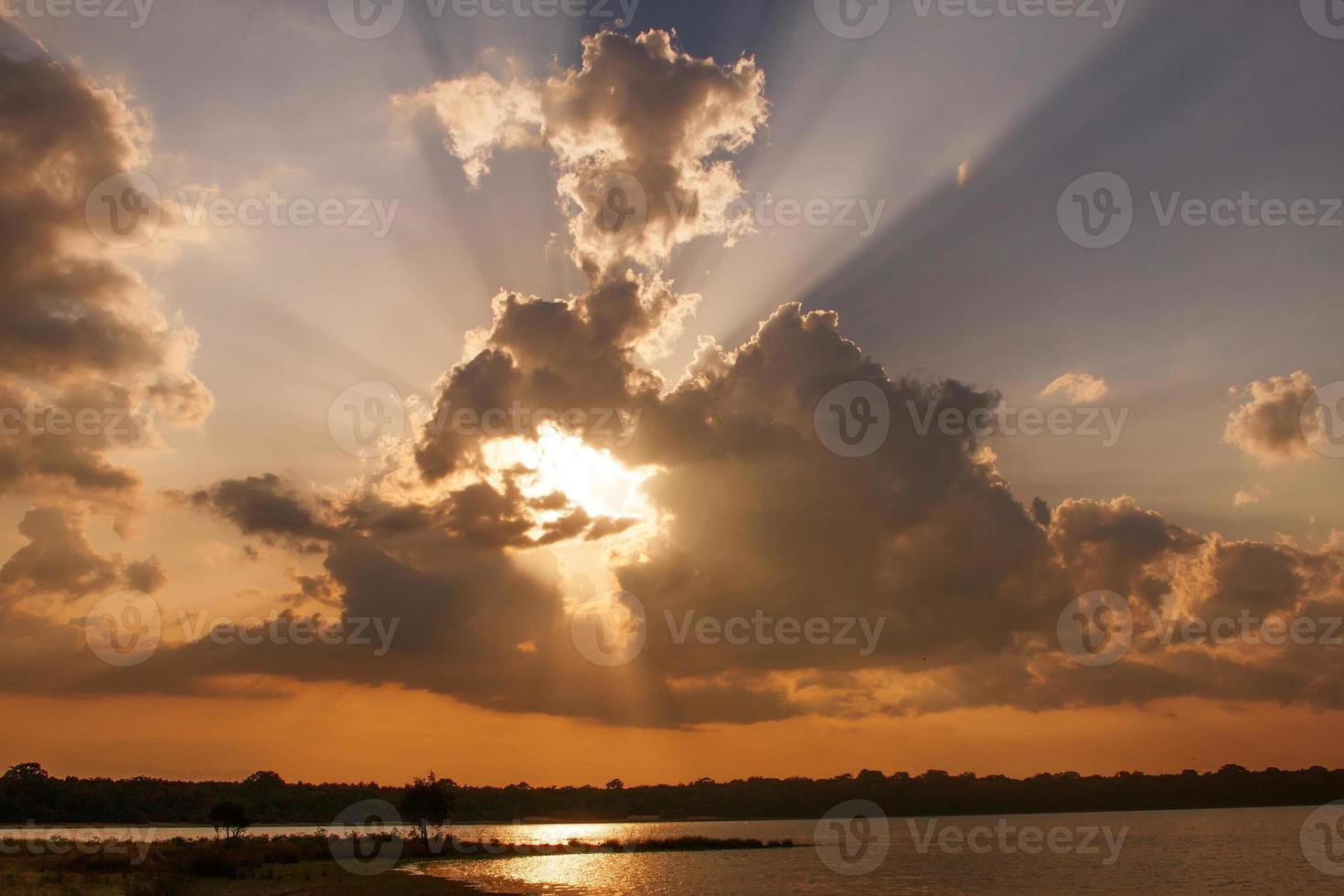 le soleil traverse les nuages au coucher du soleil photo