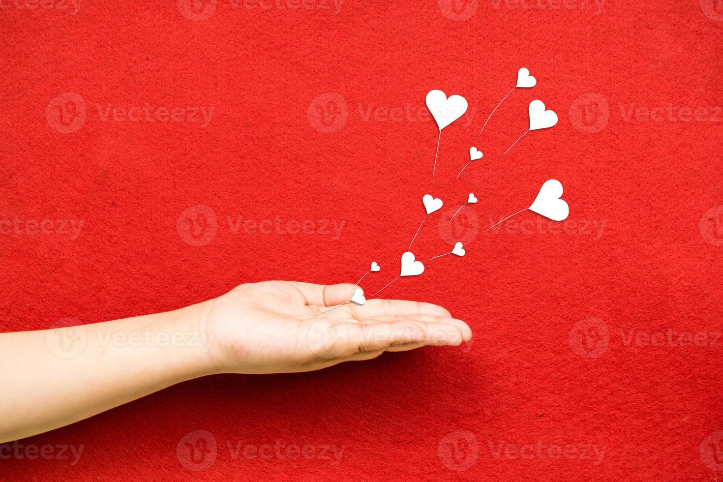 soufflant les cœurs d'une main photo