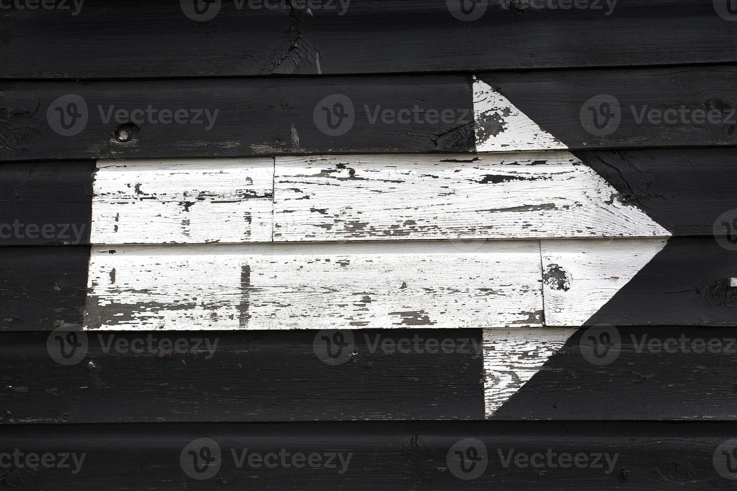 Flèche blanche peinte sur un mur de hangar en bois noir photo