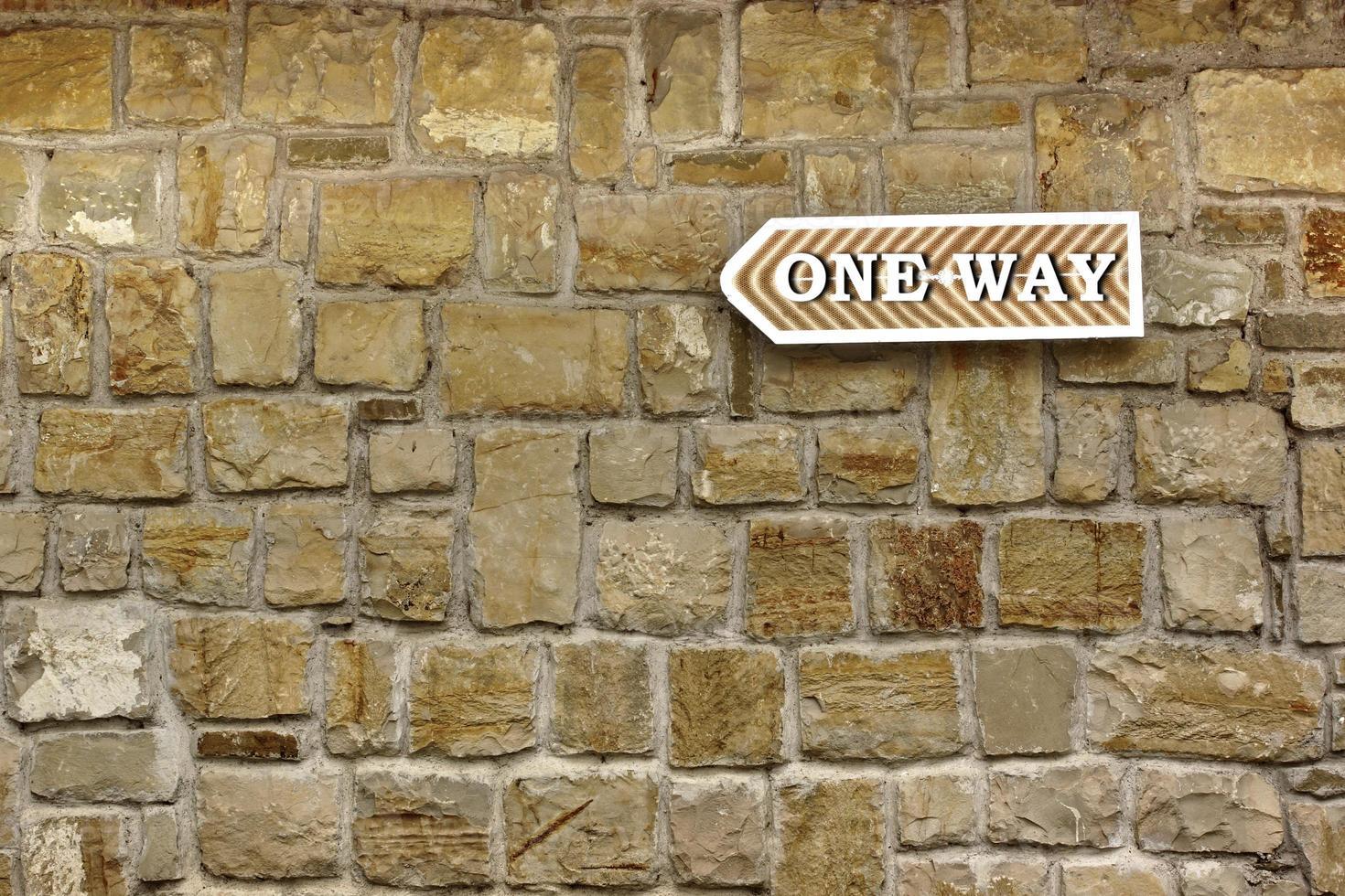 Flèche à sens unique sur le vieux mur de pierre photo
