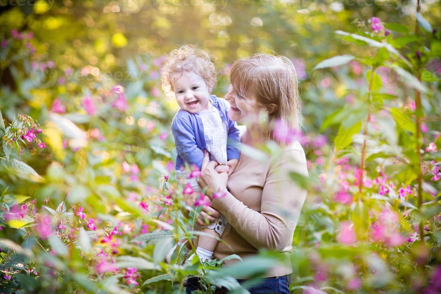 Belle femme jouant avec une petite fille en riant sur le coucher du soleil photo