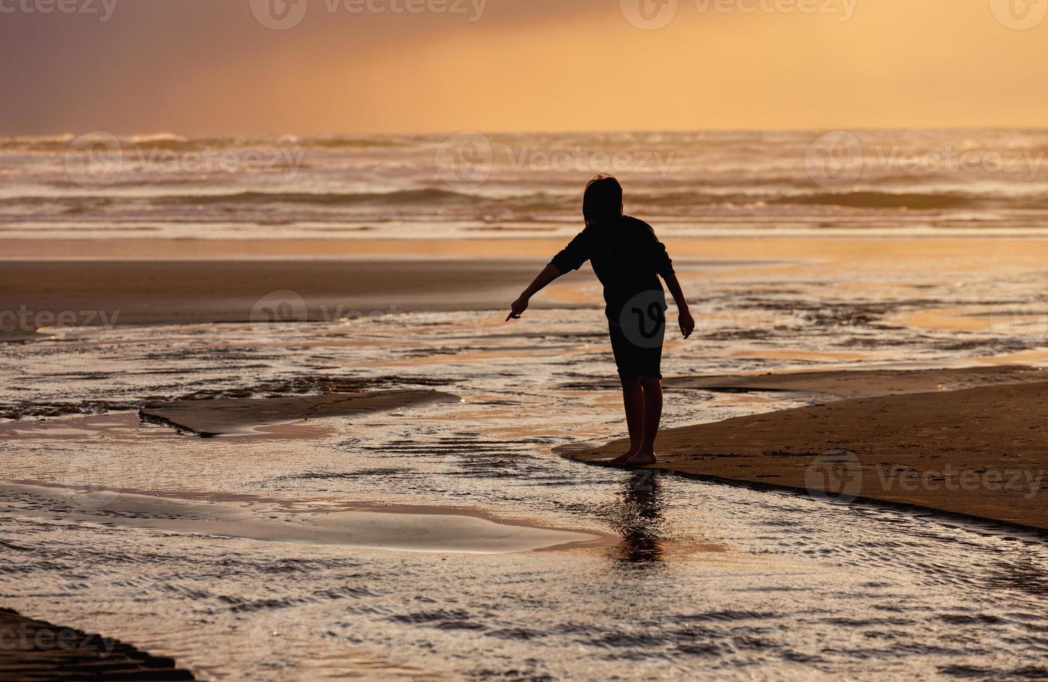 pointant vers l'eau au coucher du soleil. photo