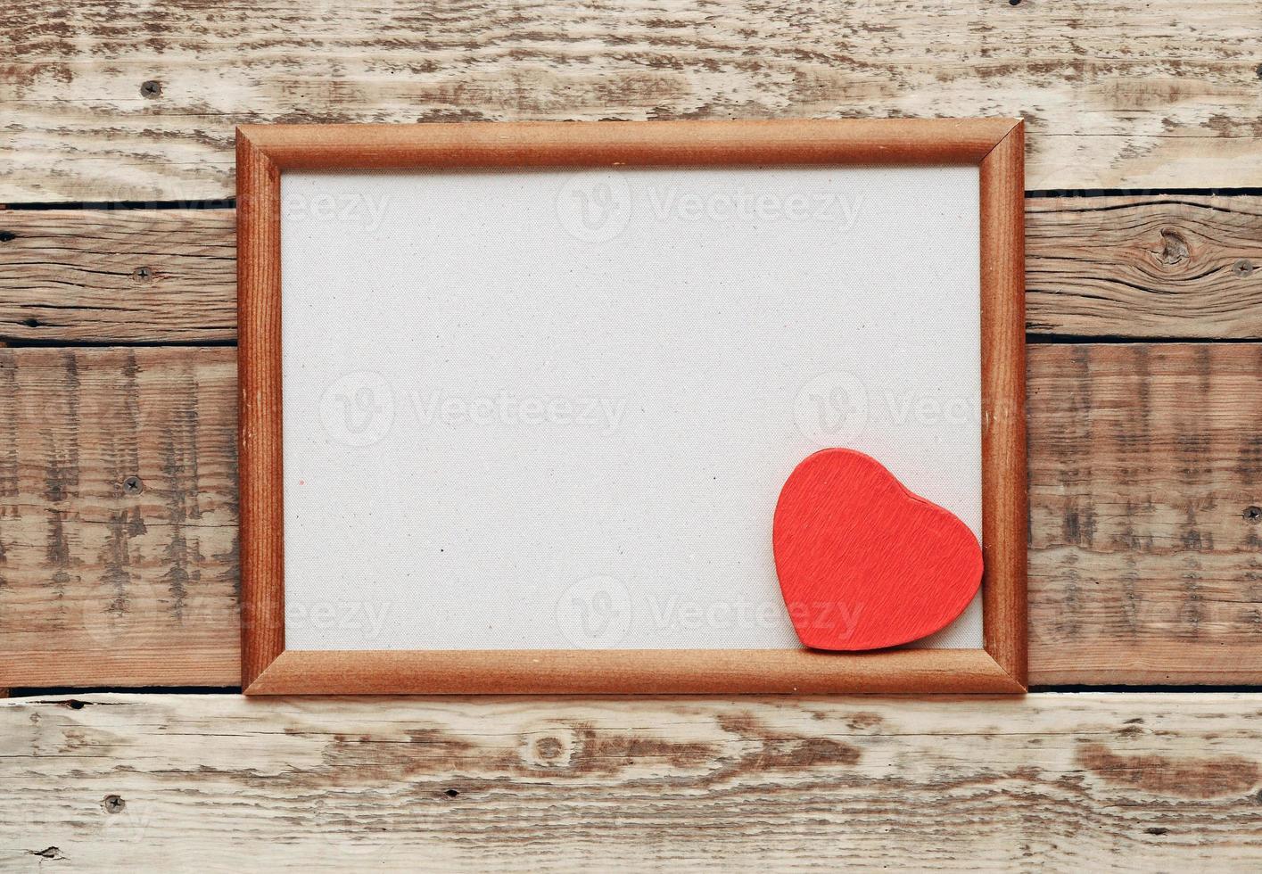coeur rouge dans un vieux cadre en bois photo