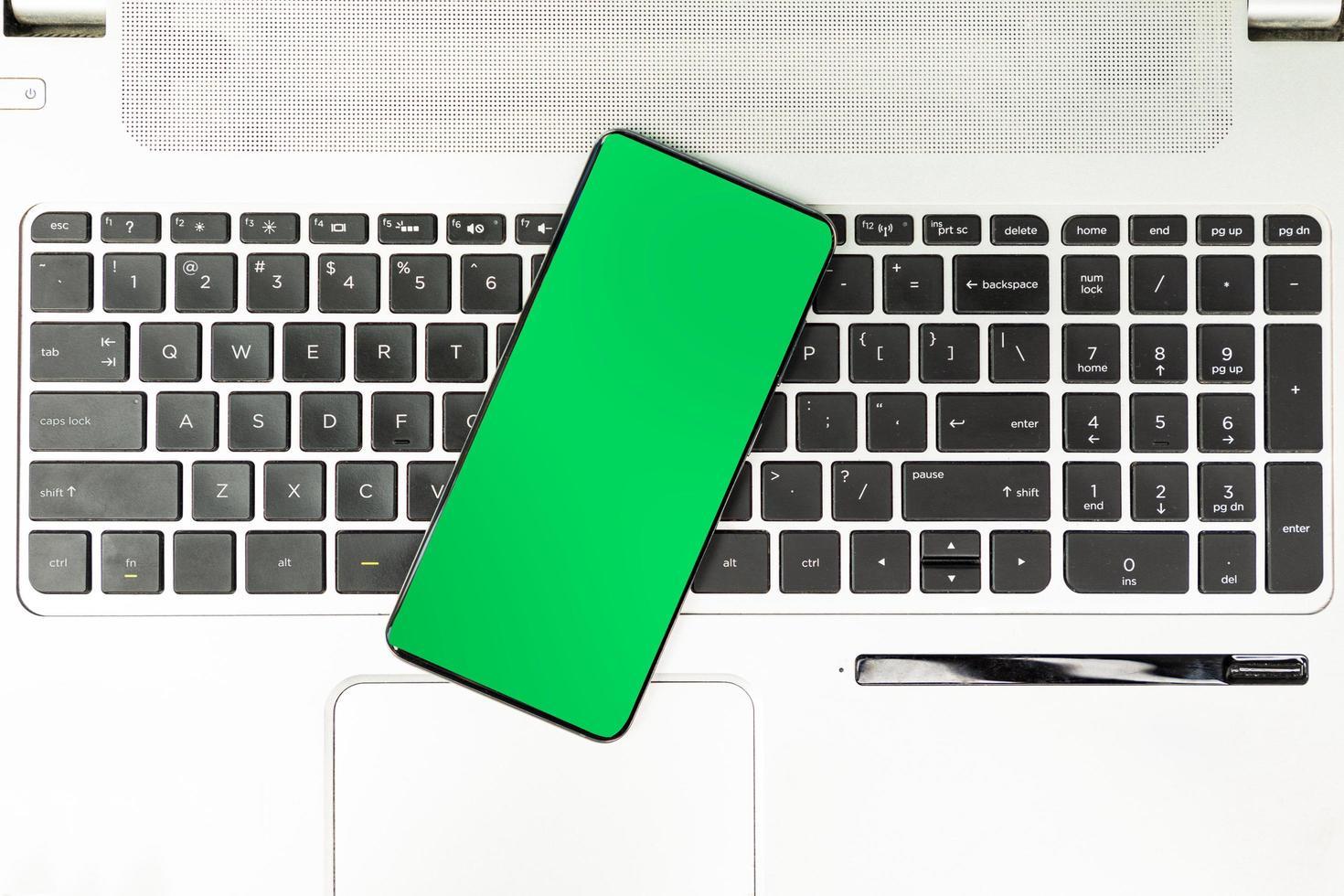smartphone écran vert sur clavier d'ordinateur portable photo