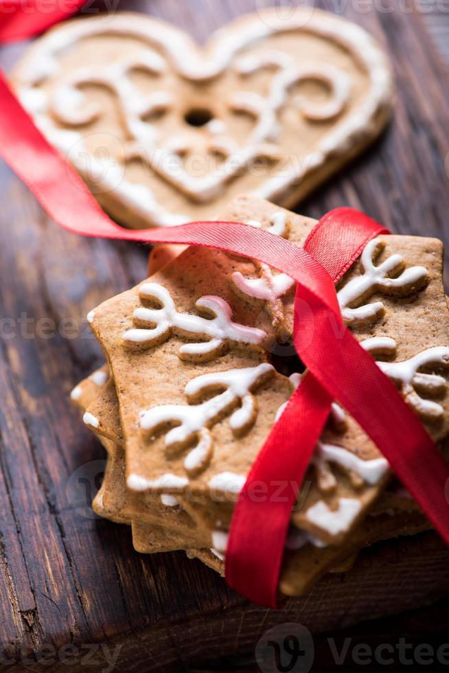 Biscuits de pain d'épice avec ruban rouge sur fond de bois photo
