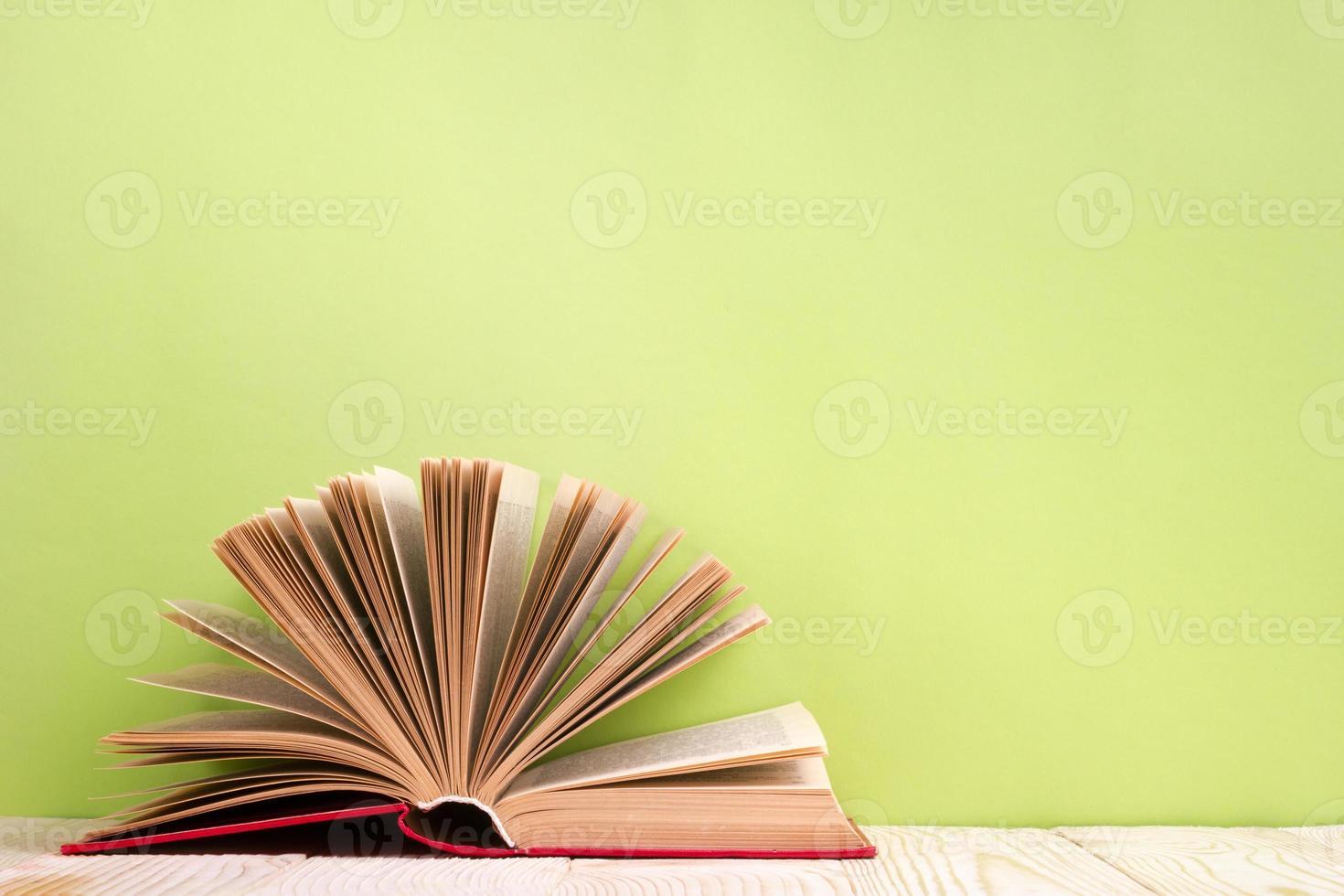Livre relié ouvert sur table en bois et fond vert photo