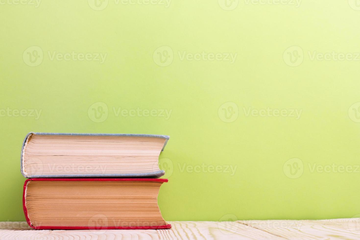 Pile de livres cartonnés colorés, livre ouvert sur fond vert photo