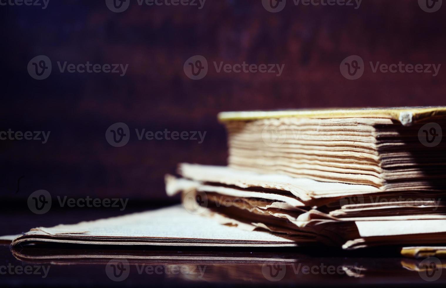 un vieux livre avec des pages déchirées sur un fond sombre photo