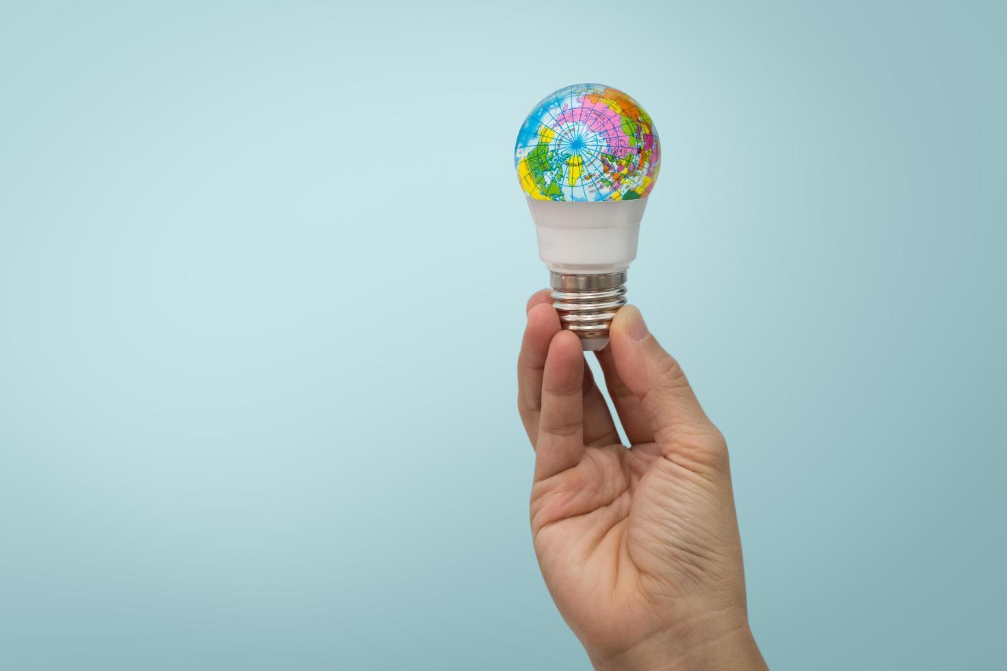 main tient une ampoule globe photo