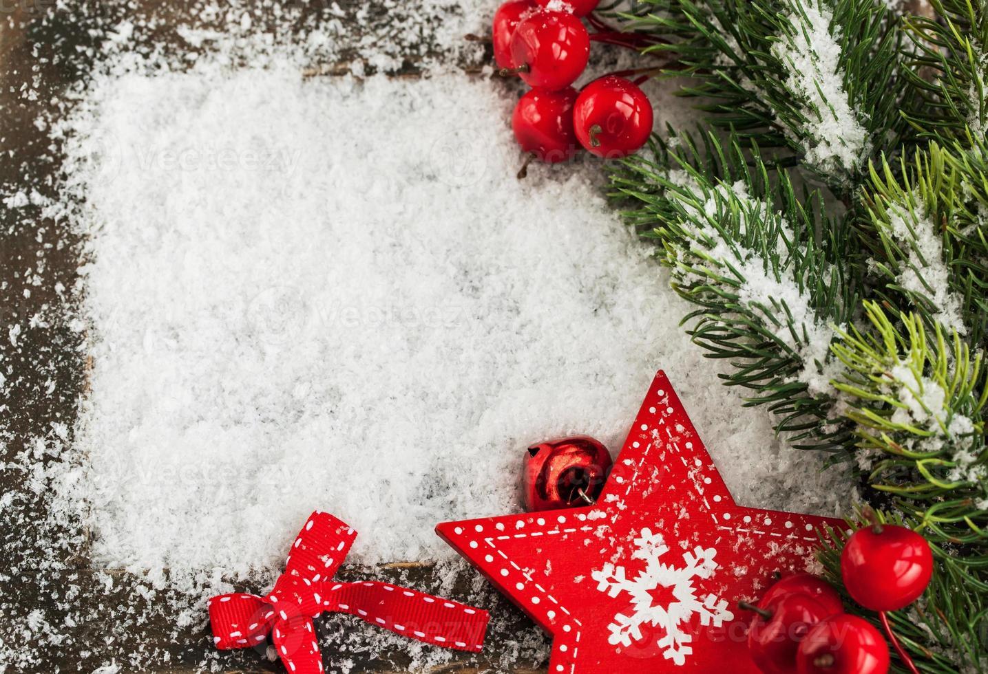 carte de noël avec neige, étoile rouge et branche de sapin photo