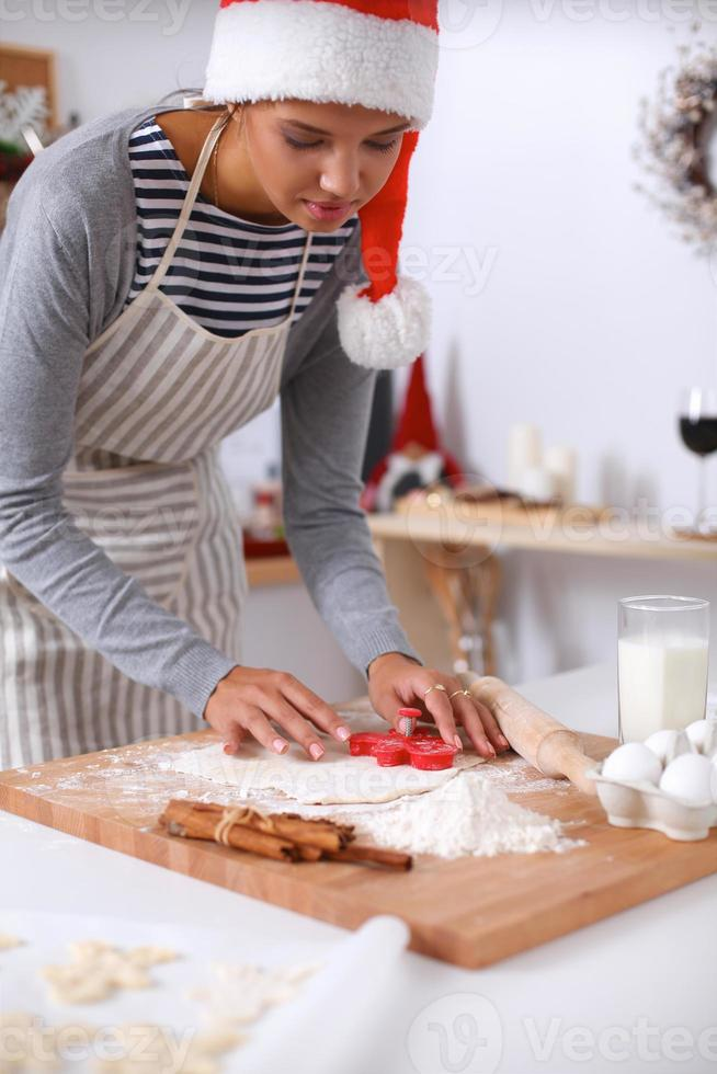 Femme faisant des biscuits de Noël dans la cuisine photo