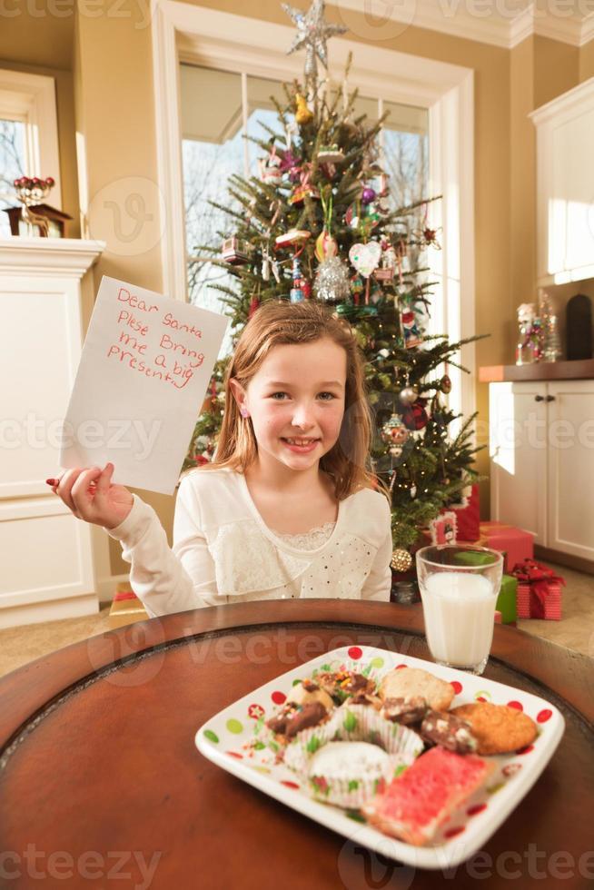 Enfant offrant des cookies et écrivant la liste de souhaits de Noël au père Noël photo