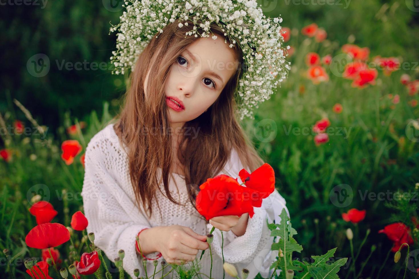 belle petite fille posant en jupe une couronne de coquelicots photo