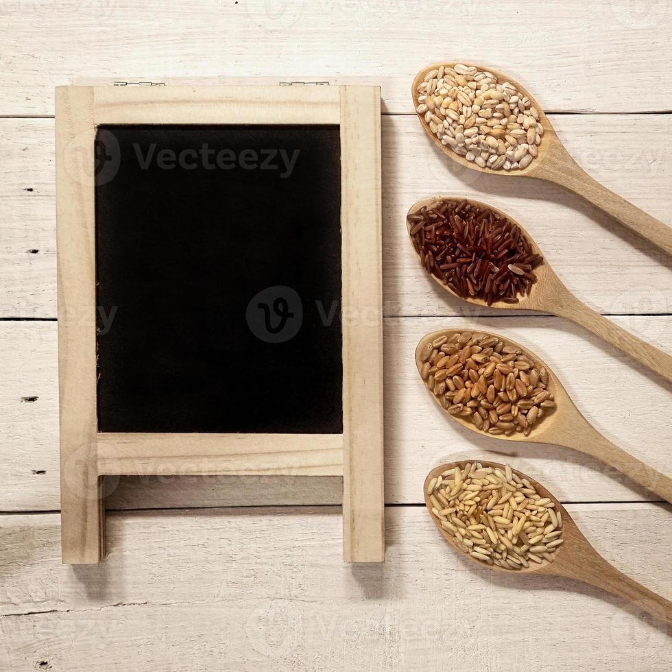 Céréales dans les cuillères et tableau noir sur table en bois photo