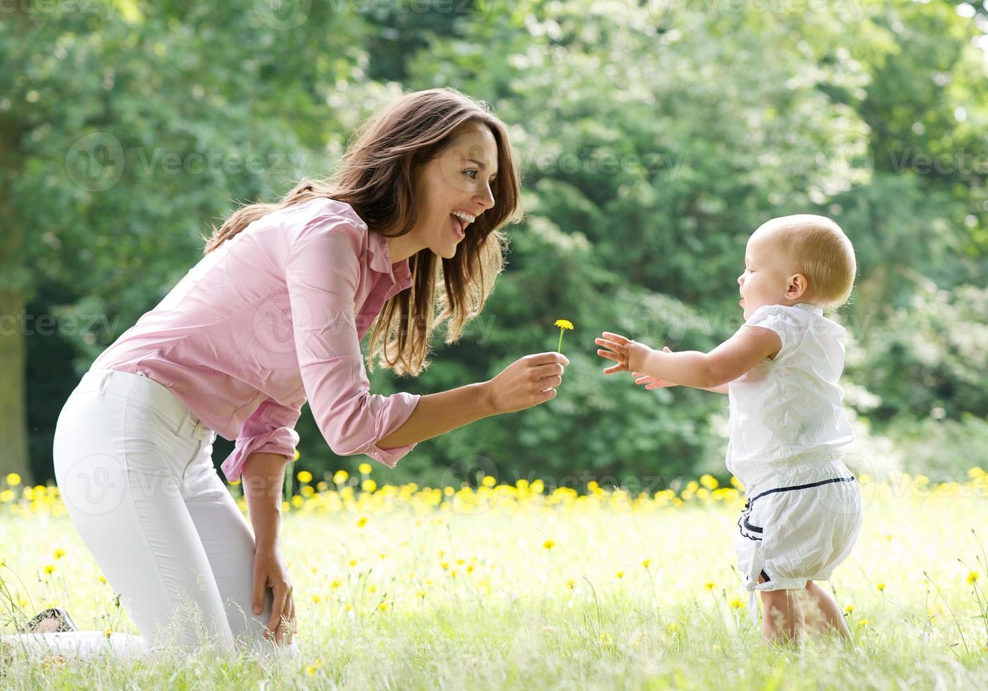 Heureuse mère apprenant à bébé à marcher dans le parc photo