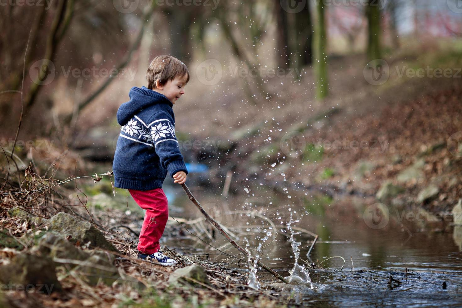petit garçon, faisant de gros éclaboussures sur un étang photo