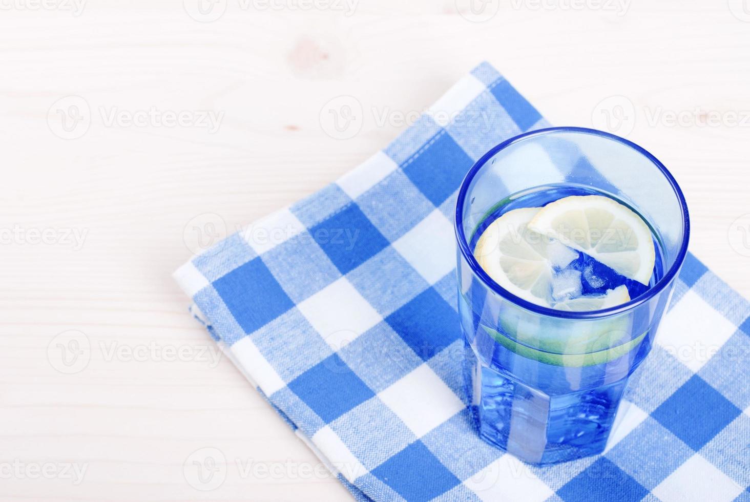 Eau de menthe citron en verre bleu sur la vue de dessus de table photo
