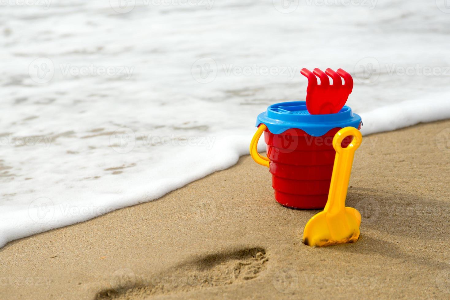 Seau rouge avec pelle, râteau et filet sur la plage photo