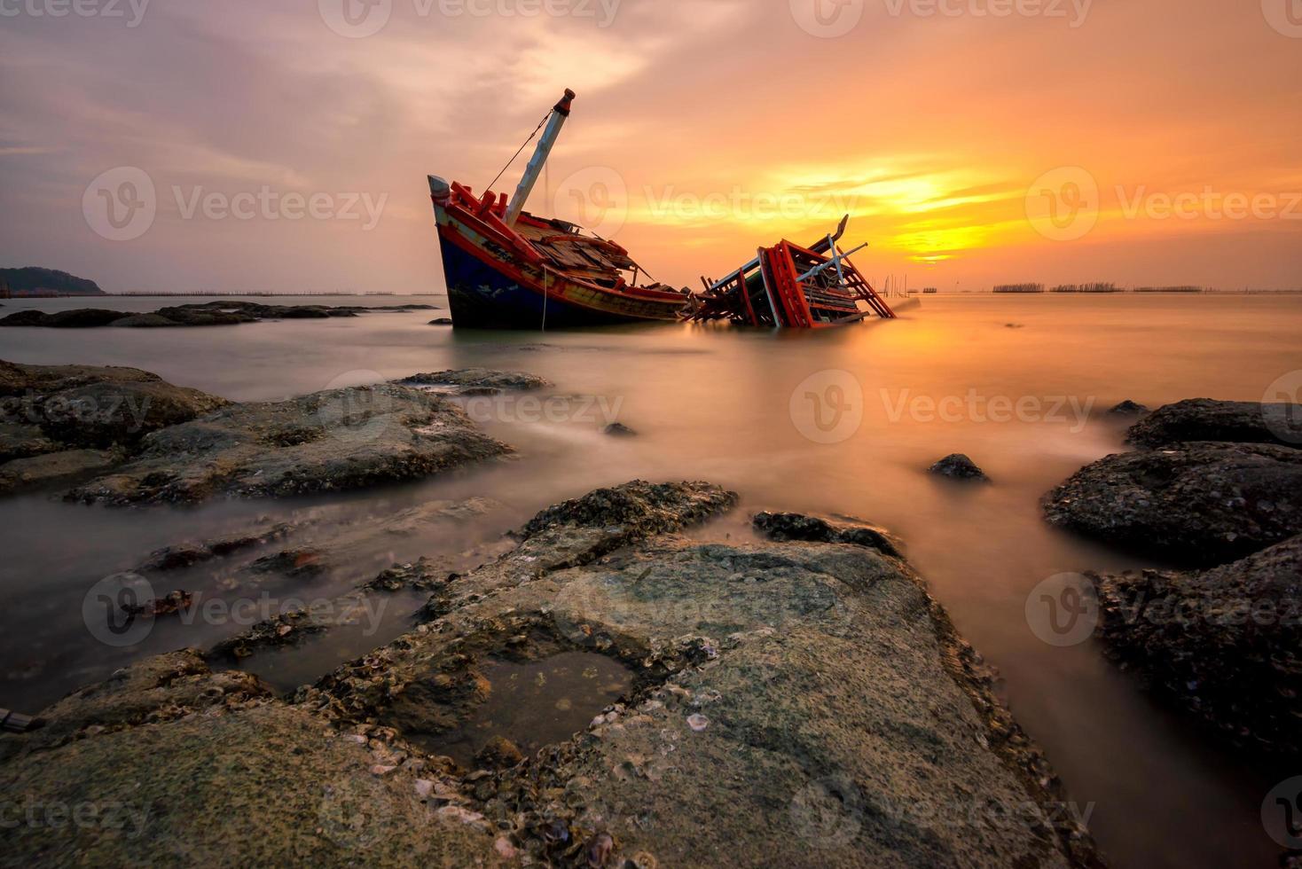 bateau de pêche échoué avec vue sur le coucher du soleil photo