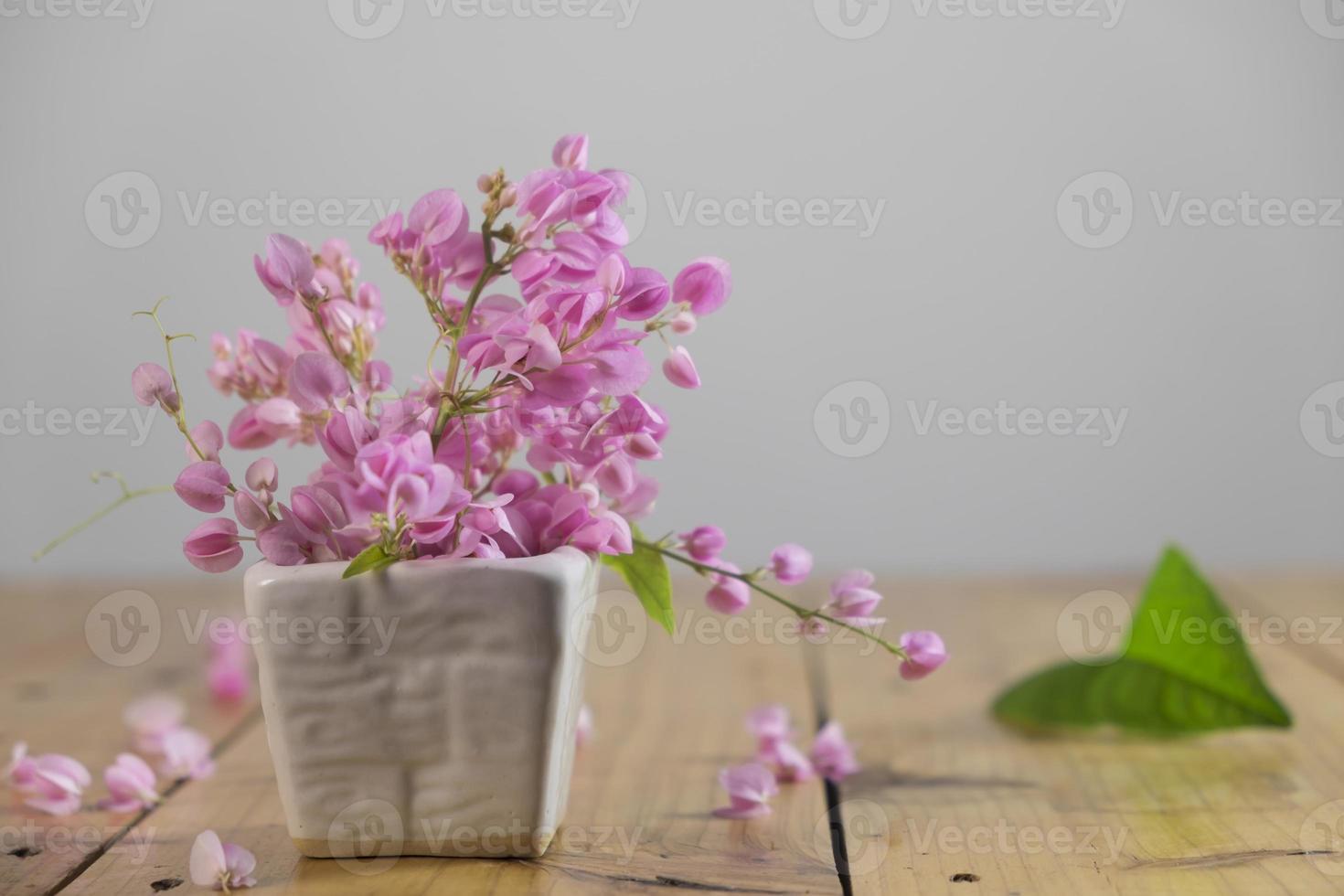 Nature morte avec fleurs roses sur table en bois photo