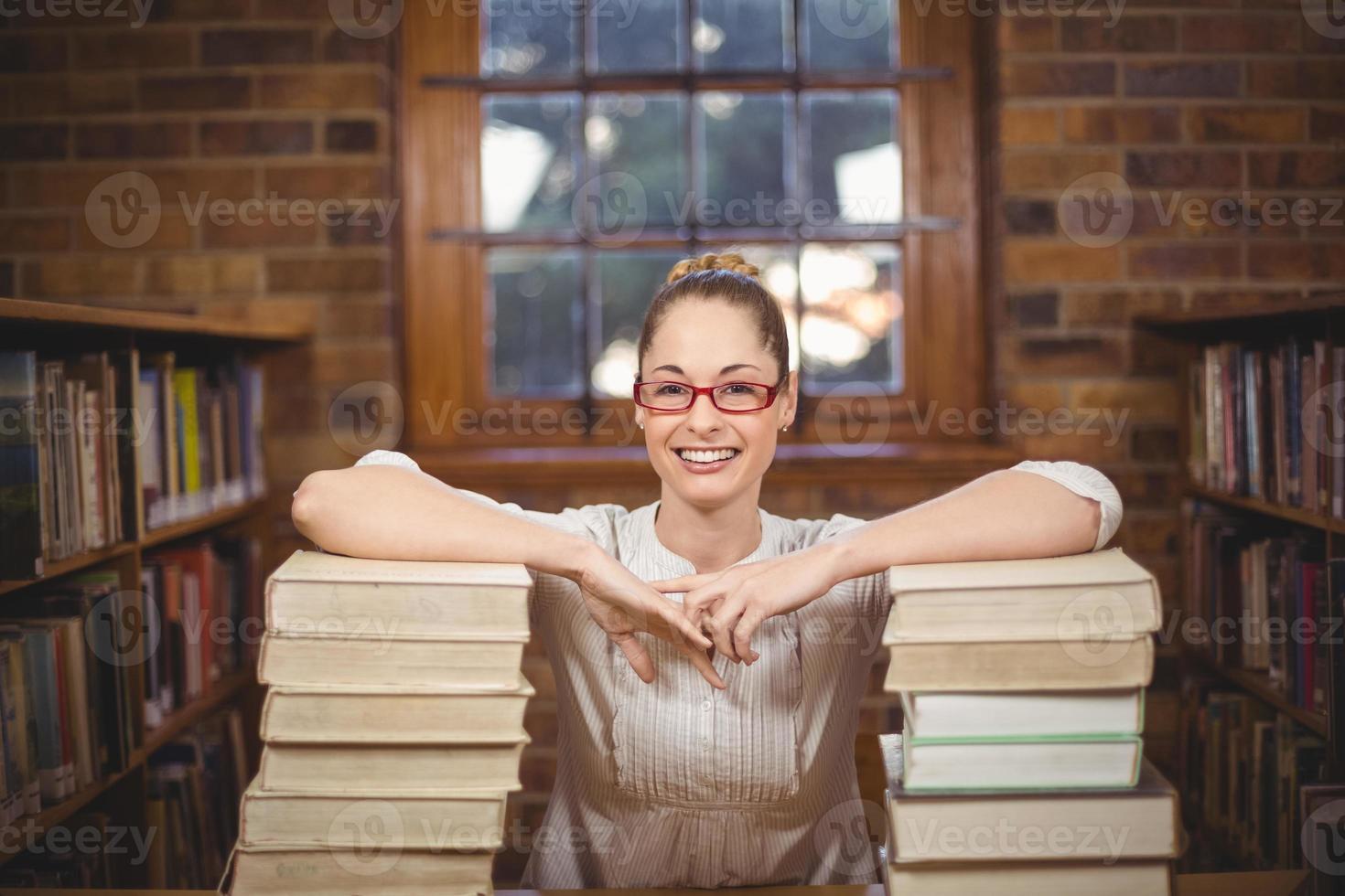 professeur blonde debout entre des livres dans la bibliothèque photo