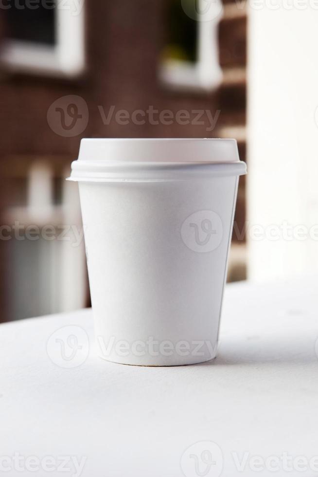 Tasse à café jetable sur le rebord de la fenêtre avec vue sur la ville en arrière-plan photo