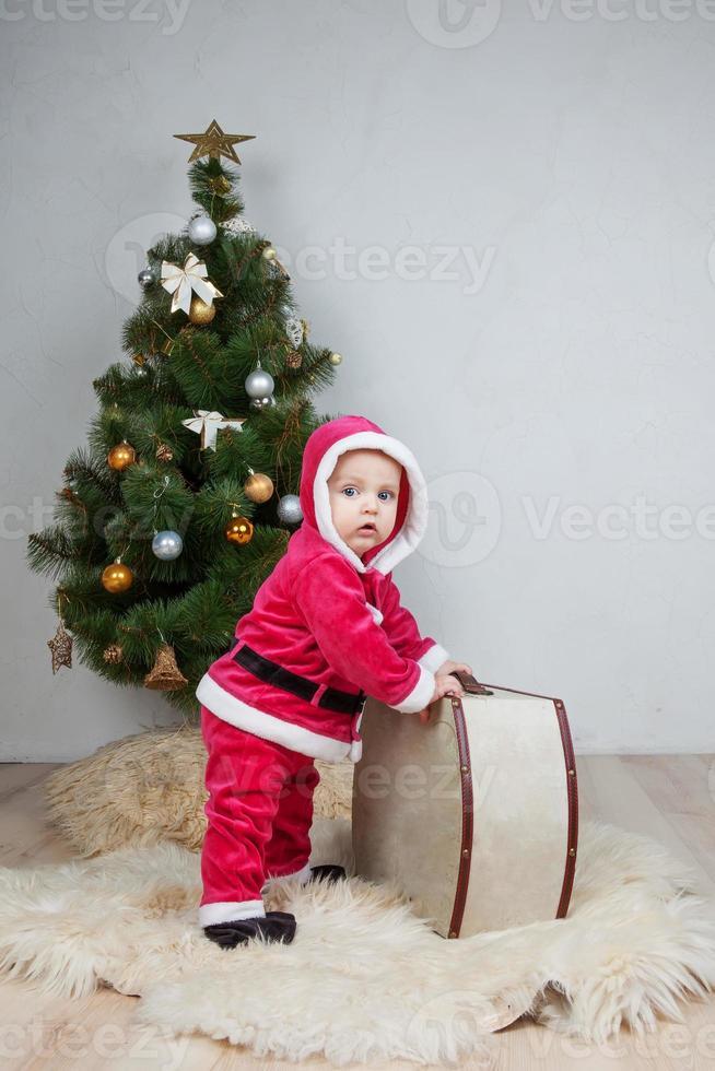 petit garçon en costume de père noël joue en studio blanc photo