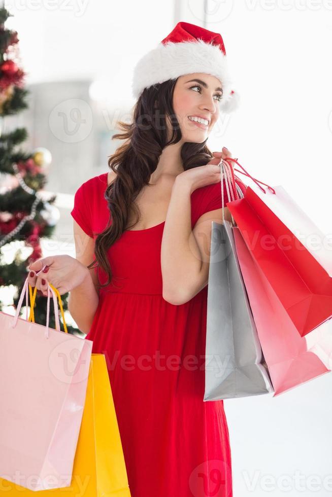 brune en robe rouge tenant des sacs à provisions photo