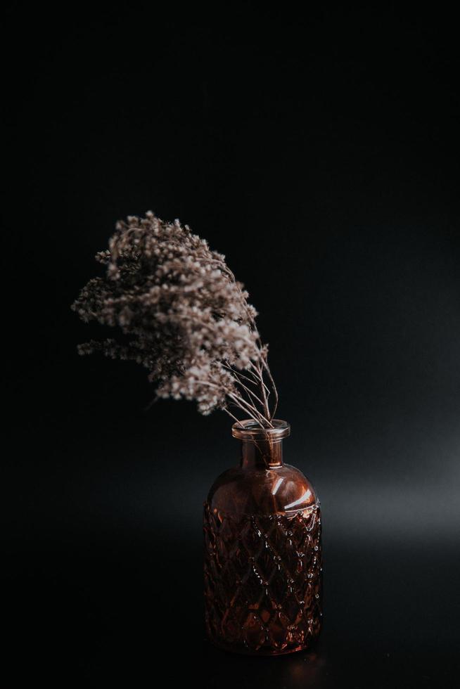 photo en niveaux de gris de fleurs sauvages séchées dans une bouteille en verre