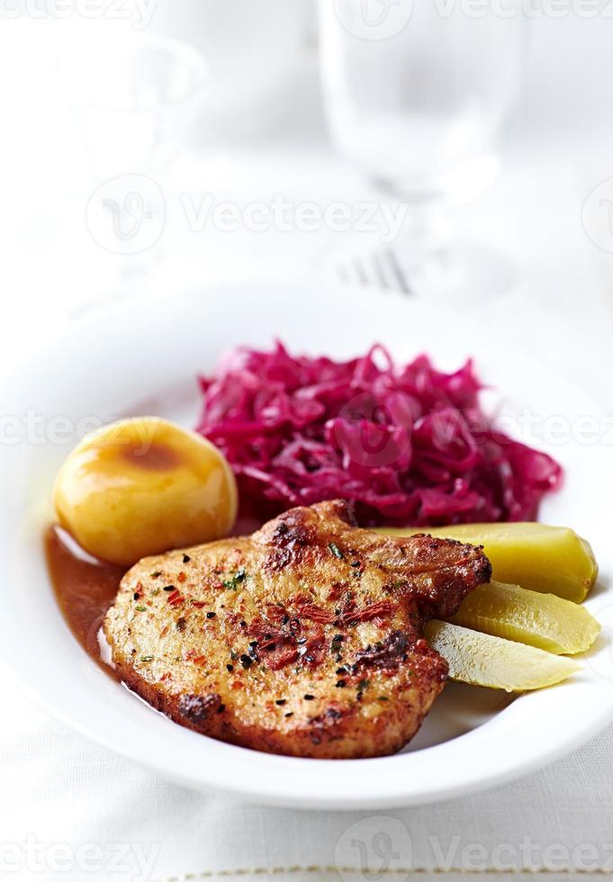 côtelette de porc rôtie avec boulettes de pommes de terre et chou rouge (Pologne) photo
