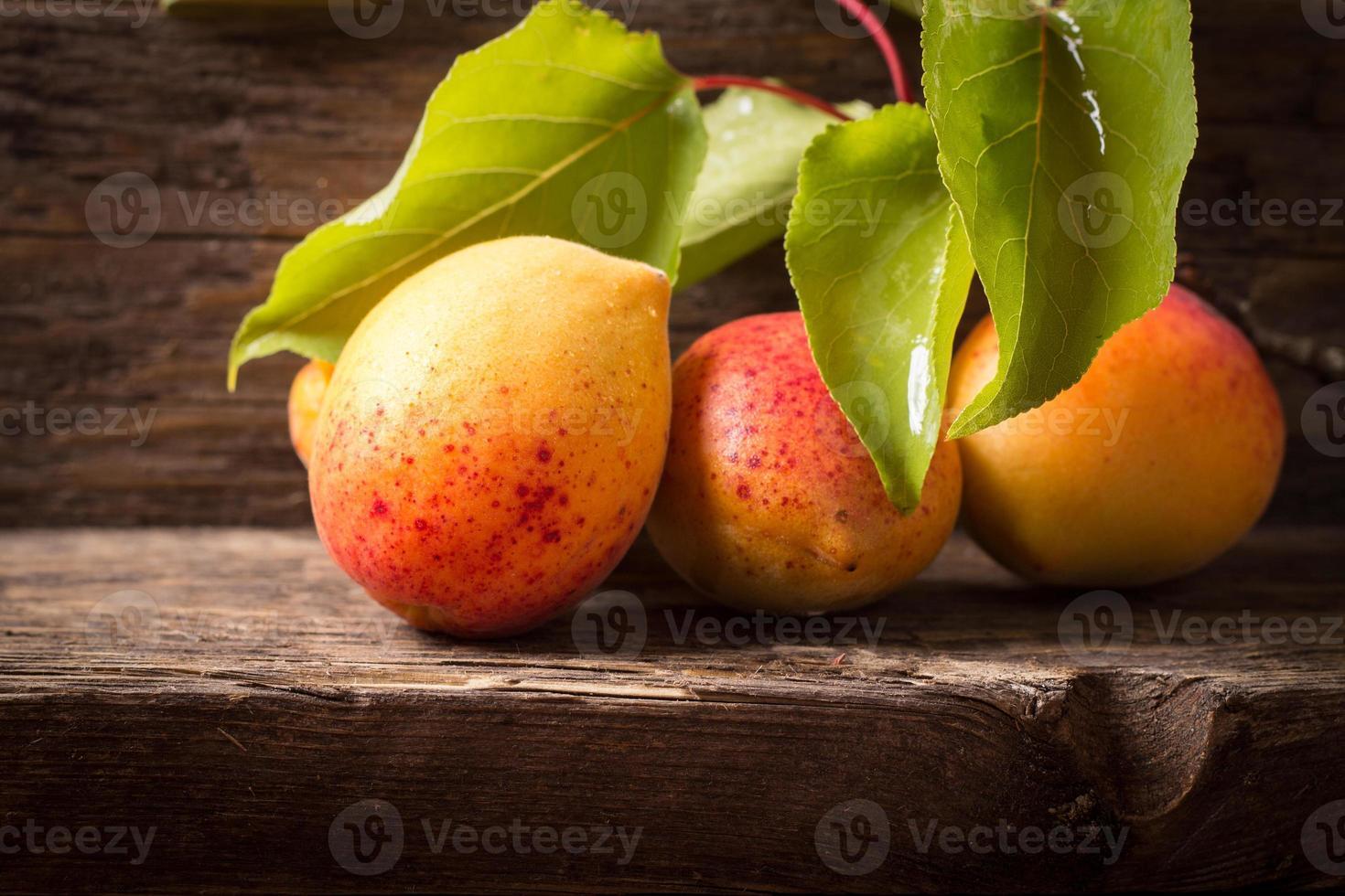 abricots avec feuille sur fond de bois photo