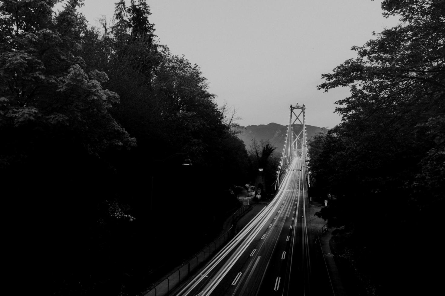Photographie en niveaux de gris de véhicules circulant sur la route pendant la journée photo
