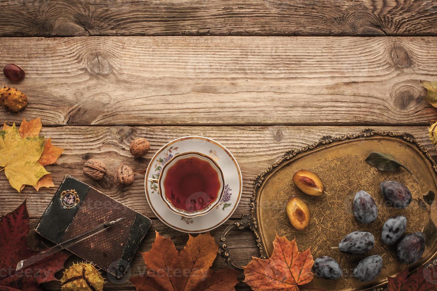 prunes, noix et feuilles avec cahier vintage et thé horizontal photo