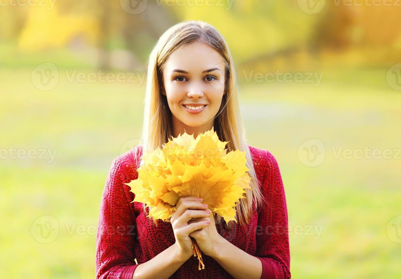 Portrait de la belle femme souriante avec des feuilles d'érable jaune automne photo