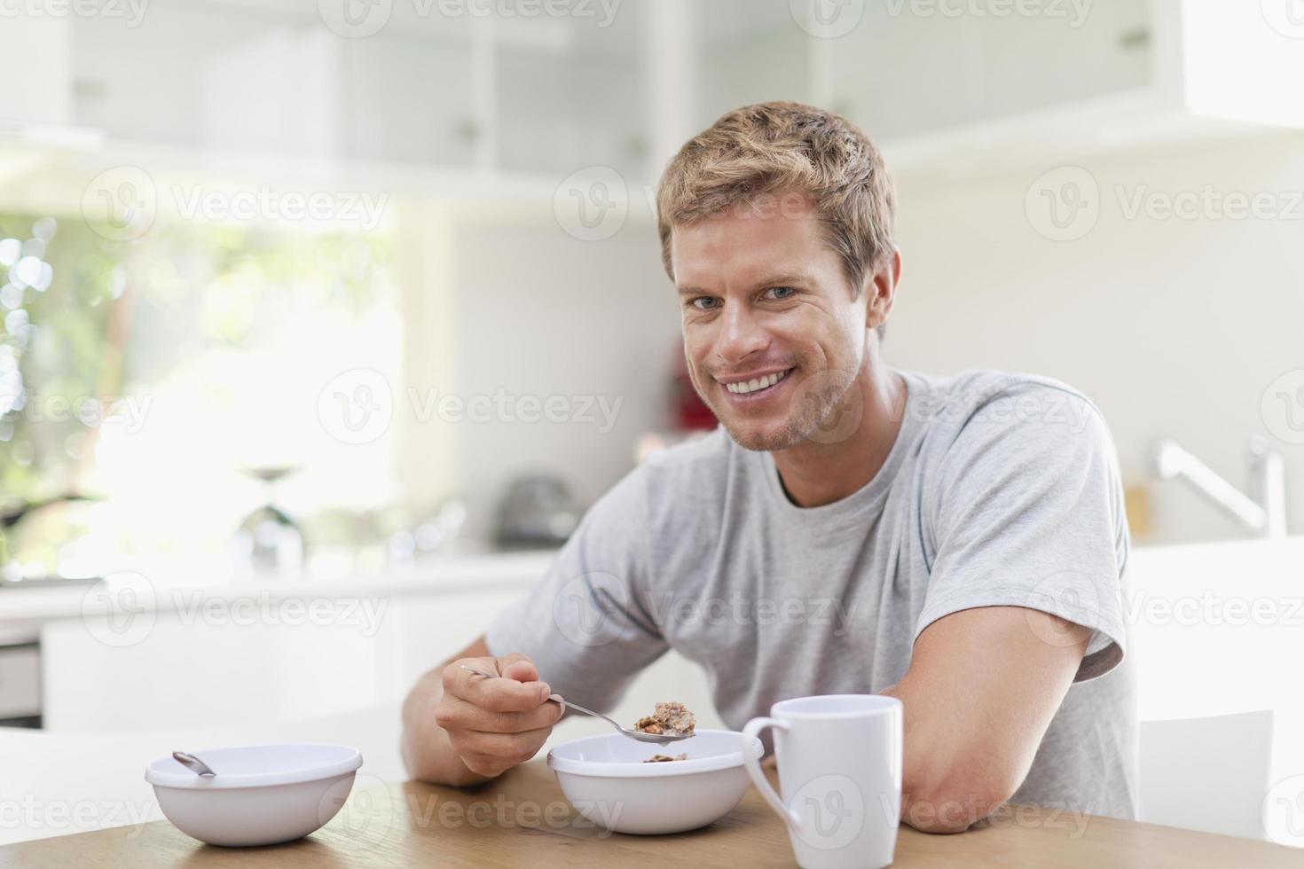 homme mangeant le petit déjeuner dans la cuisine photo