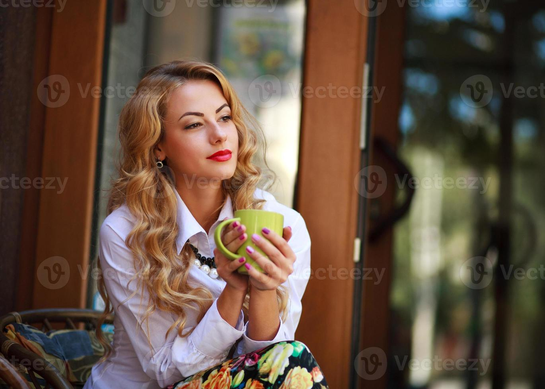 Femme pensive assise avec une tasse de café à l'extérieur photo