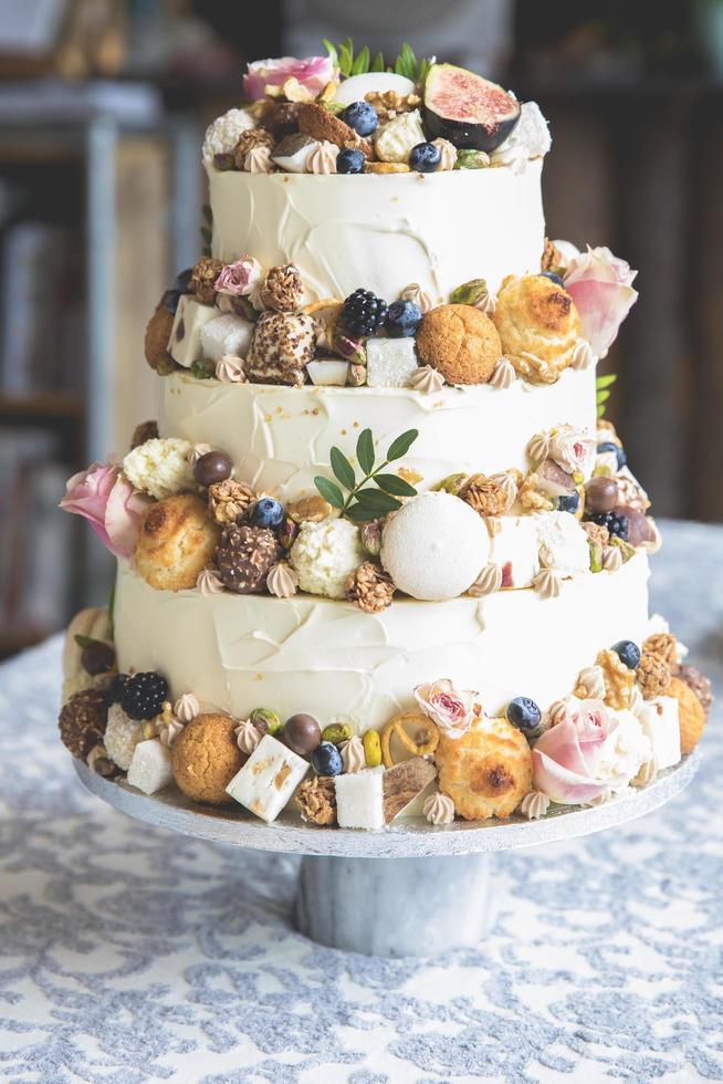 gâteau de mariage décoratif avec fruits, biscuits, macarons et fleurs photo