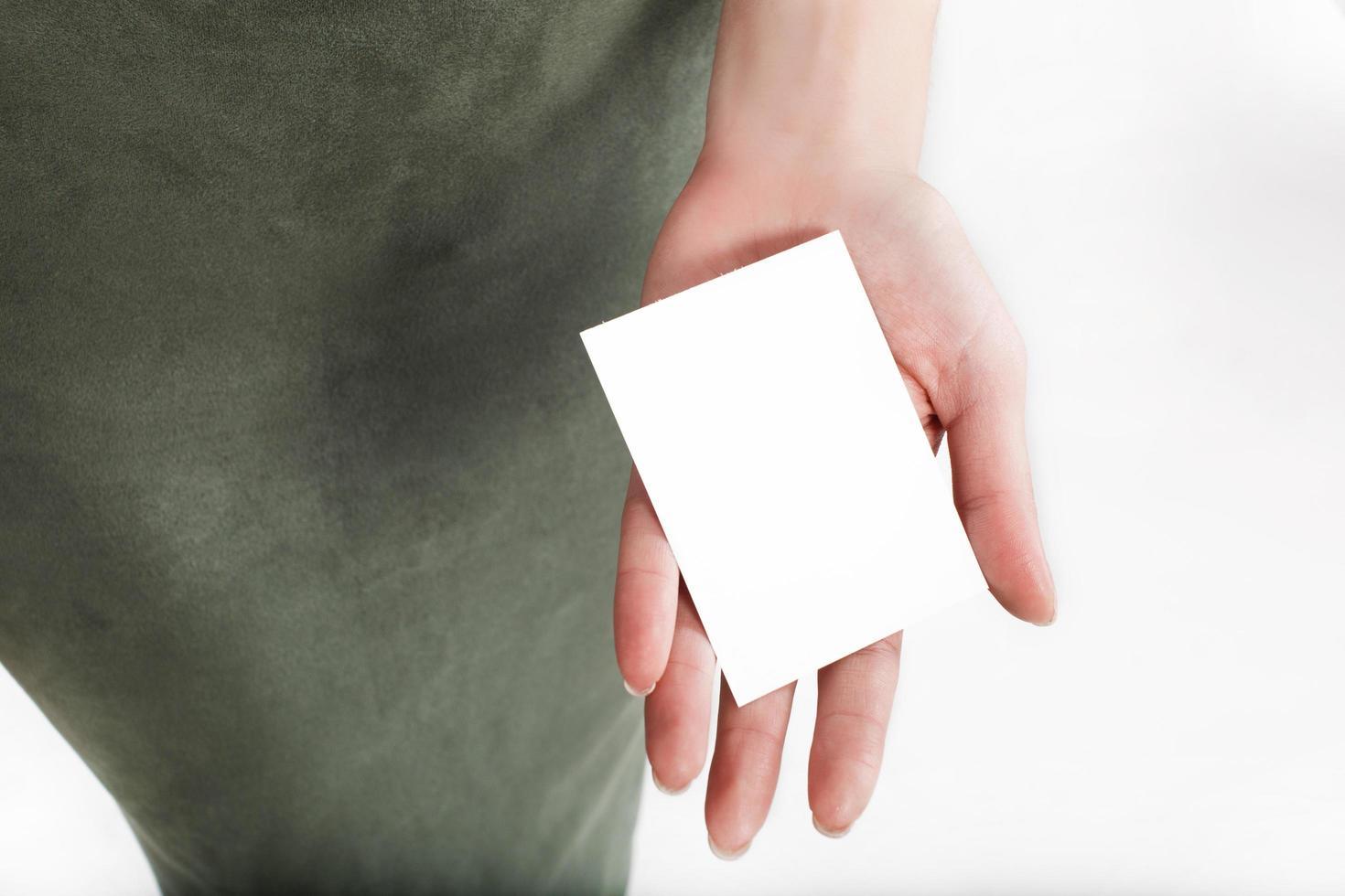 femme tient une carte blanche dans sa main photo