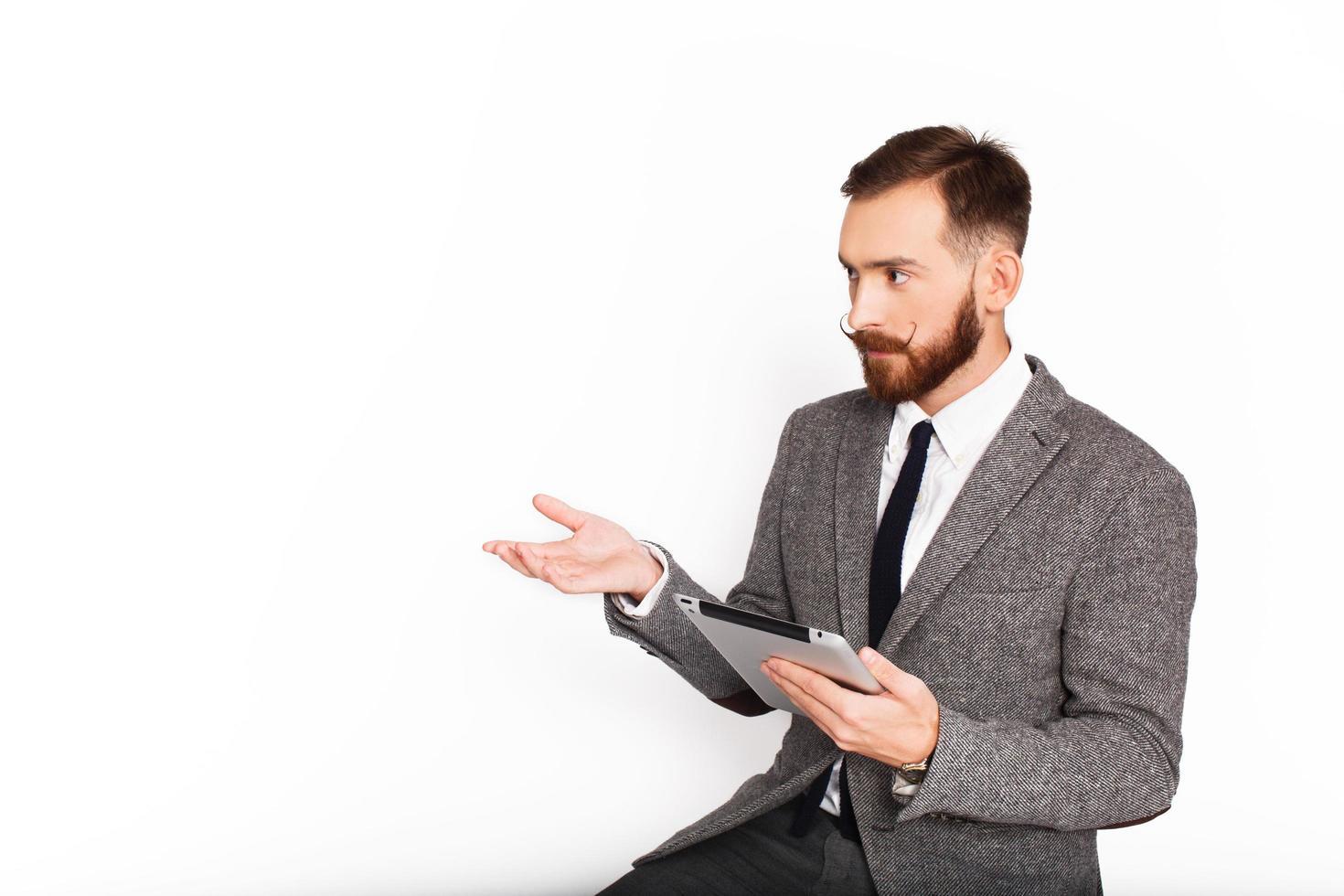 homme sérieux en costume gris gesticulant tout en tenant une tablette photo