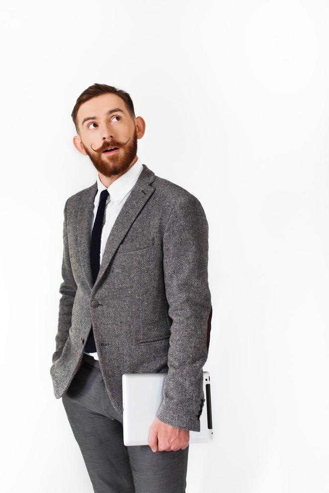 Homme surpris avec barbe rouge pose en costume gris avec tablette à la main photo
