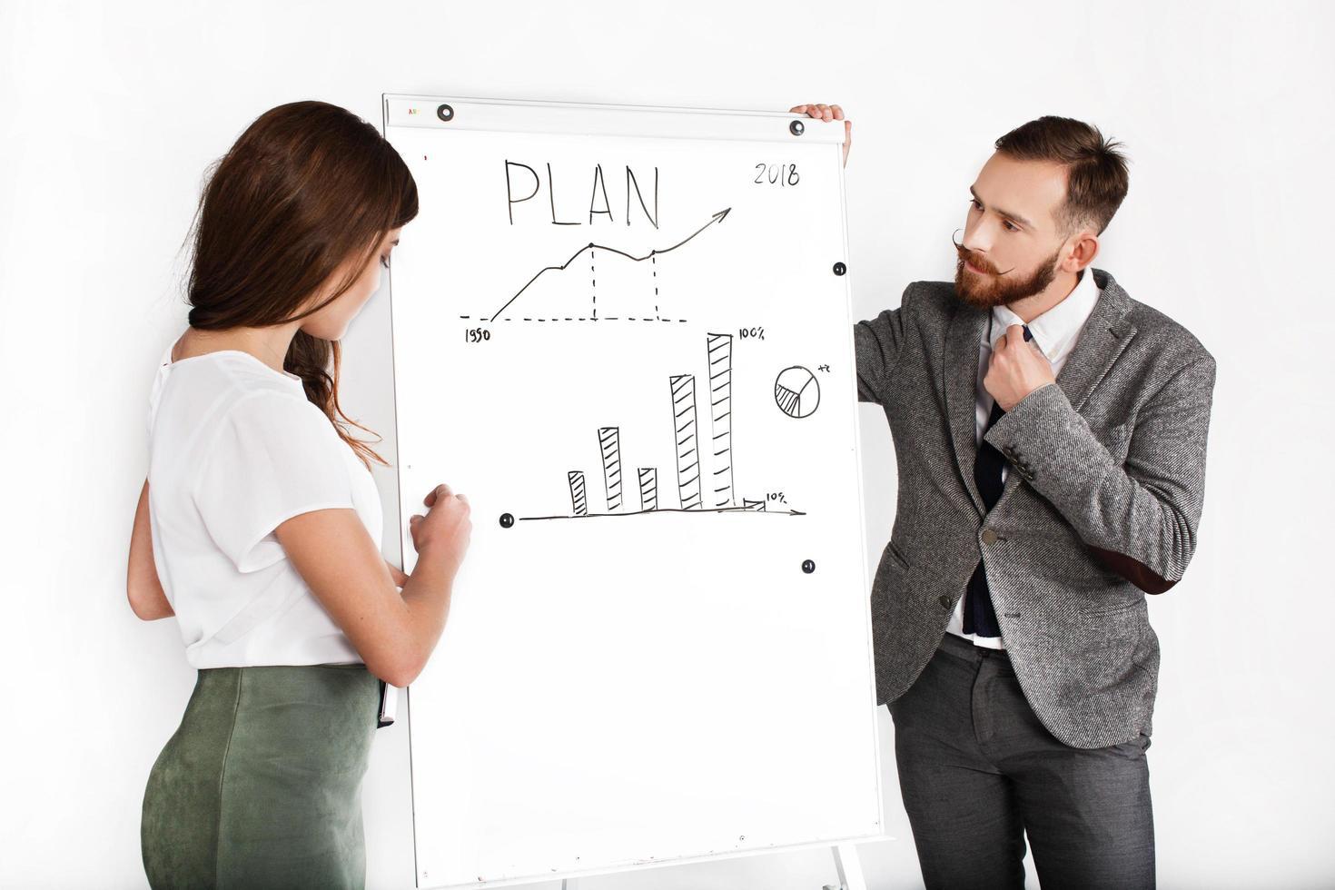 homme d & # 39; affaires et femme discutent graphique écrit sur tableau blanc photo