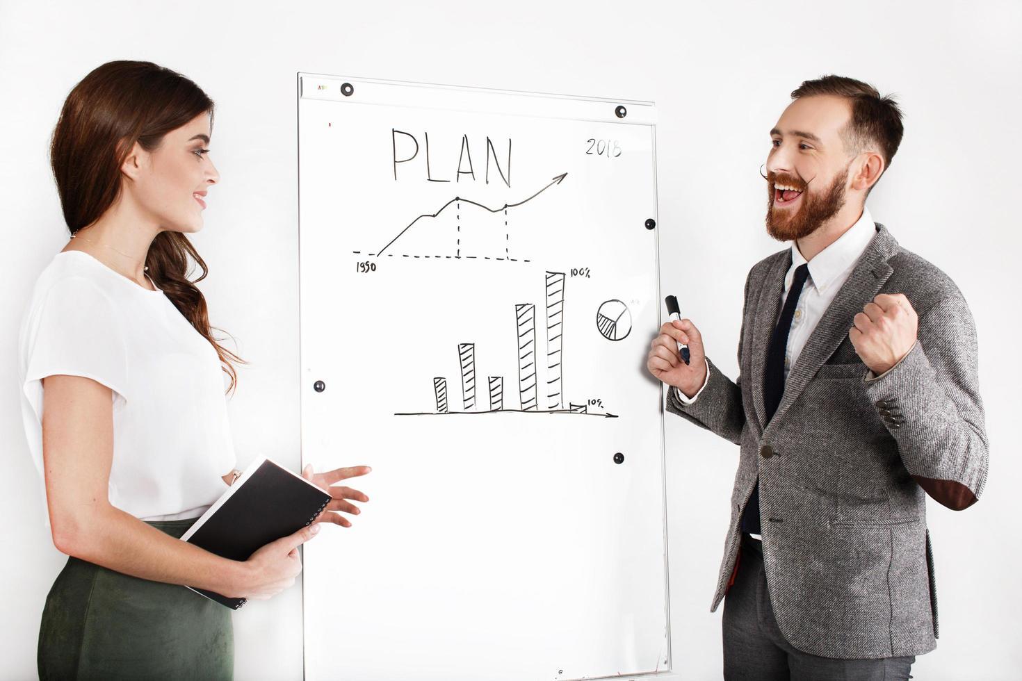 joyeux homme et femme discutent graphique sur tableau blanc photo