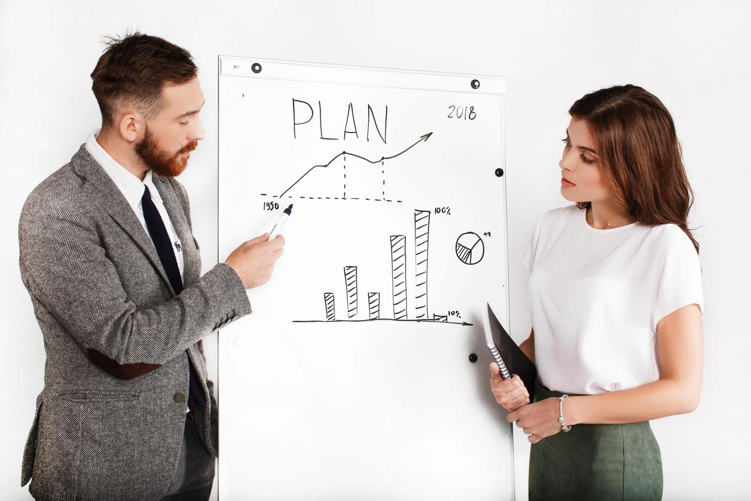 homme d & # 39; affaires et femme débat sur le graphique sur tableau blanc photo