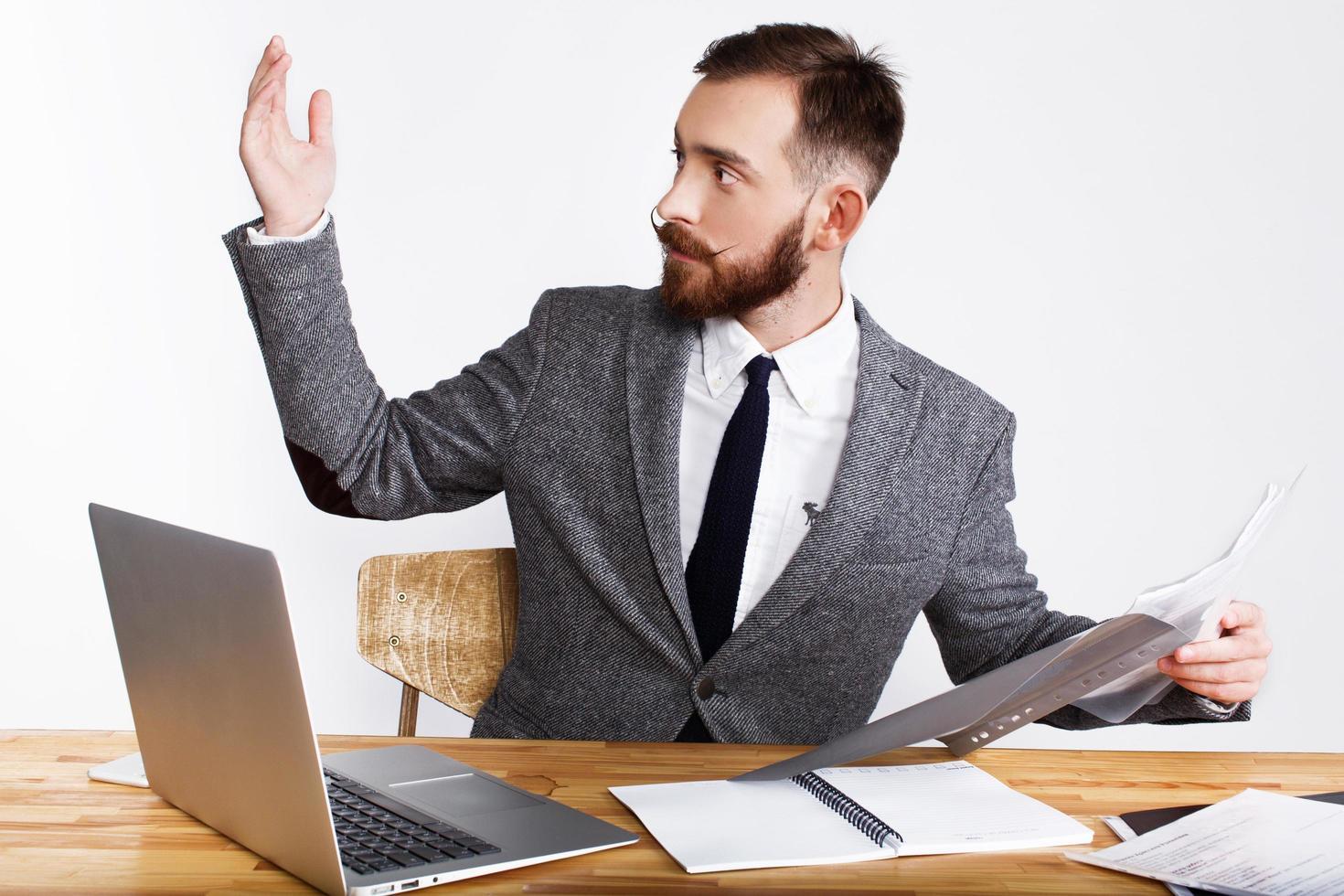 homme d & # 39; affaires lève la main assis au bureau photo