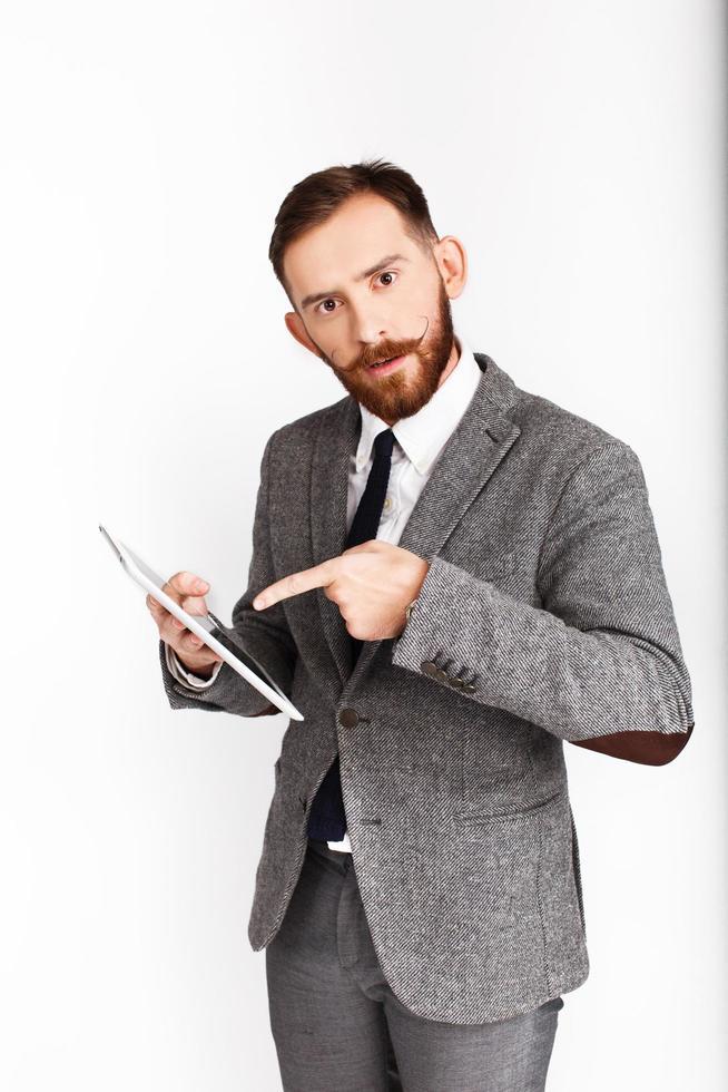 homme barbu en costume gris montre sa tablette photo