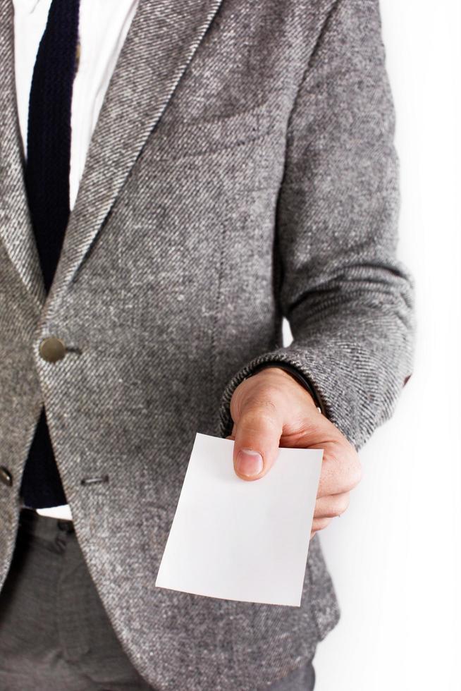 homme en costume gris tient une carte blanche vierge photo
