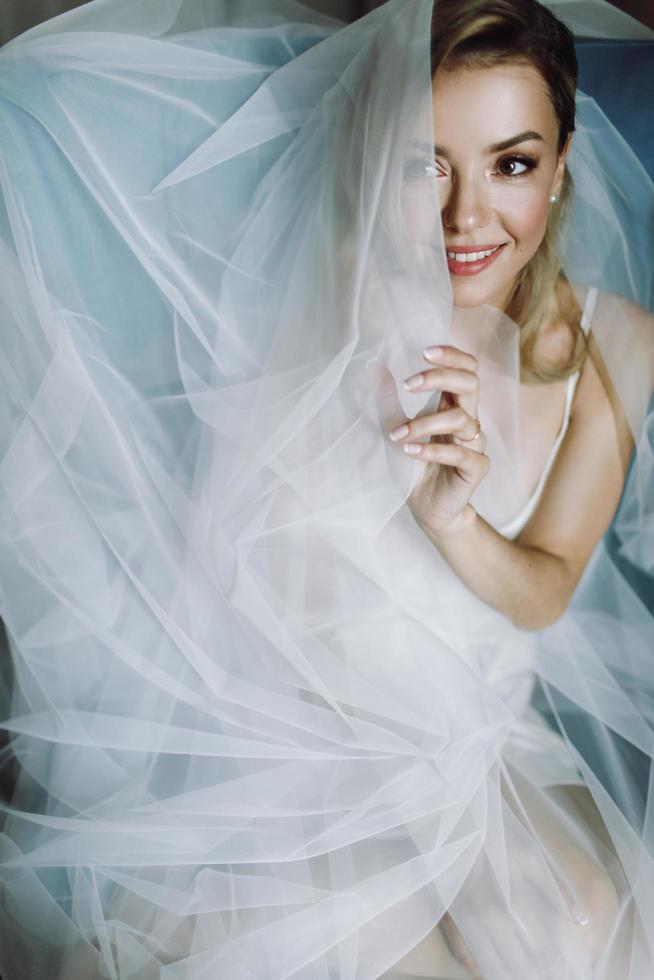 superbe mariée blonde aux yeux profonds cachés sous un voile bleu photo