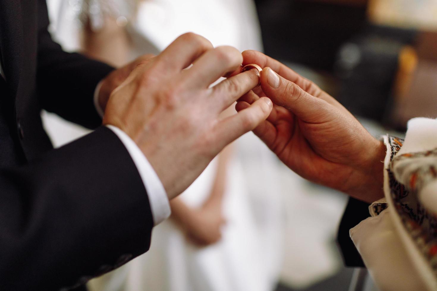 Prêtre met la bague de mariage sur la main du marié photo